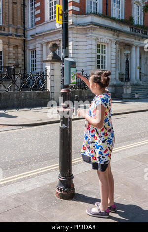 A child taps a key fob onto a 'Beat the Street' box on a lampost to register distance walked. - Stock Image