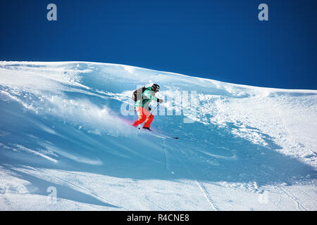 Skier freerides or downhill. Backcountry ski with space for text - Stock Image