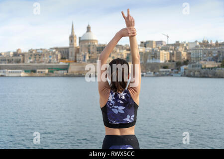 woman standing infront of Valletta, Malta, with her arms outstretched, travel freedom. - Stock Image