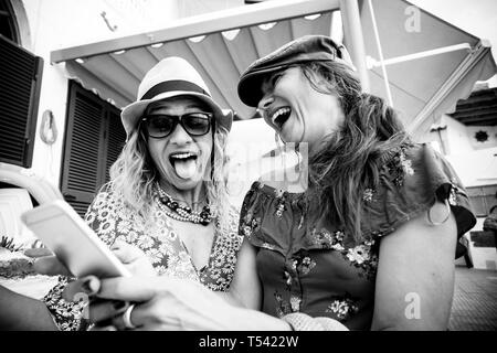 Black and white couple of young crazy women have fun together laughing a lot and doing expression taking a selfie picture with the phone - friendship  - Stock Image