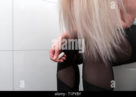 woman sitting on toilet with tampon in her hand to illustrate menstruation. - Stock Image