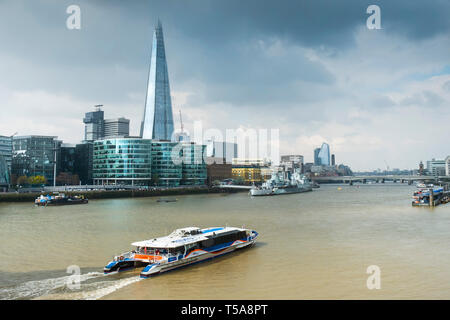 A Thames Clipper river boat on the River Thames with The Shard and other iconic buildings in the background. - Stock Image
