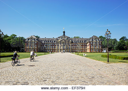 People ride bicycles approaching Westphalian Wilhelm University of Münster, Germany. - Stock Image