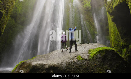 Low angle view of couple taking pictures with smartphone standing on mossy boulder near waterfall in remote landscape - Stock Image