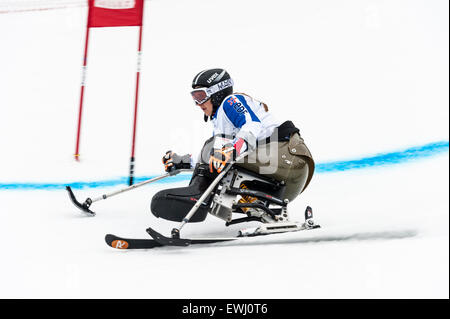 A disabled competitor, using specially-adapted ski equipment, passing through a gate in a giant slalom race - Stock Image