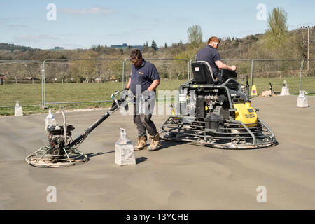 Presteigne, Powys, Wales, UK. Men using power trowels (power floats) to smooth the surface of a freshly laid concrete slab floor - Stock Image