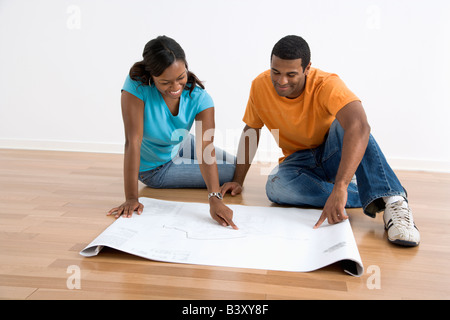 African American male and female couple sitting on floor looking at architectural blueprints - Stock Image