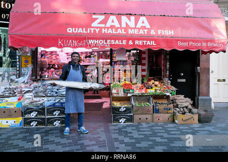 Electric Avenue Brixton street market a man worker holding barracuda fish outside Zana Halal meat & fish in South London SW9 England UK  KATHY DEWITT - Stock Image