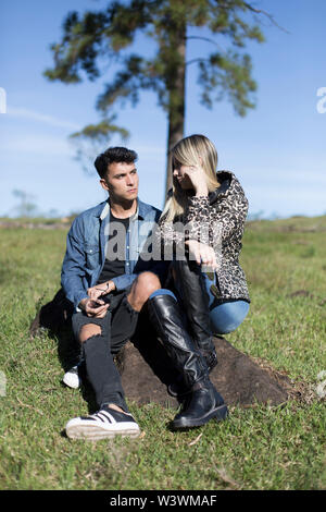 Man and woman sitting in the sun, with sunglasses on an autumn day - Stock Image