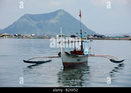 A Filipino maneuvers his boat on Taal Lake with a view of Volcano Island in the background near Tagaytay City, Philippines. - Stock Image