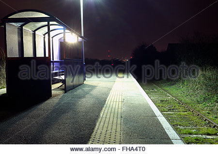 Illuminated waiting shelter on platform during the night, at Severn Beach railway station, South Gloucestershire, - Stock Image