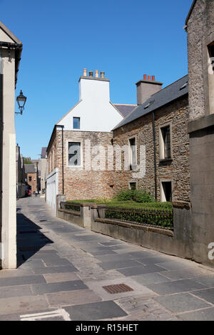 An old sandstone house in Stromness, Orkney with paving stones from a local quarry and cobble stones in the centre of the street. - Stock Image