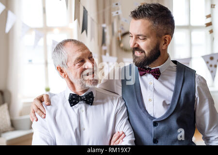 A portrait of a senior and mature man standing indoors in a room set for a party. - Stock Image