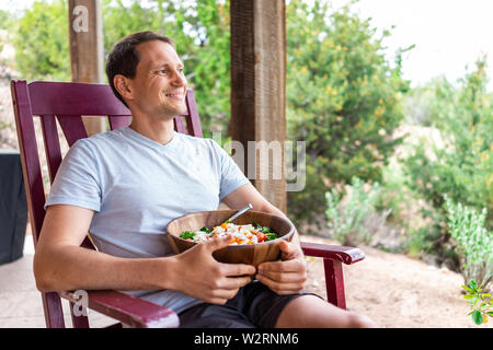 Happy man holding fresh salad in wooden bowl with lettuce sitting on rocking chair in garden patio - Stock Image