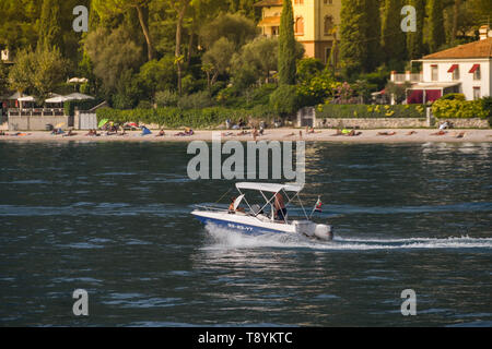 LAKE GARDA, ITALY - SEPTEMBER 2018: Two people on a small boat with outboard motor cruising on Lake Garda. - Stock Image