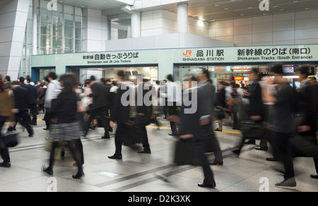 Workers commuting to work at the busy Shinagawa Station in Tokyo Japan - Stock Image