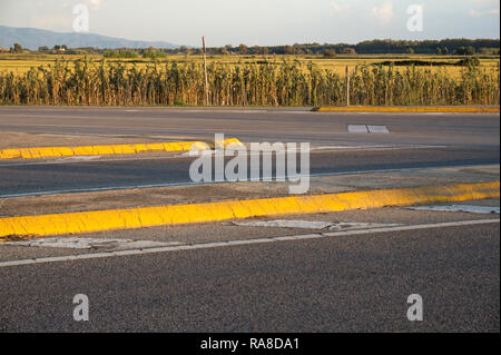 yellow curbs and countryside near Oristano, Sardinia, Italy - Stock Image