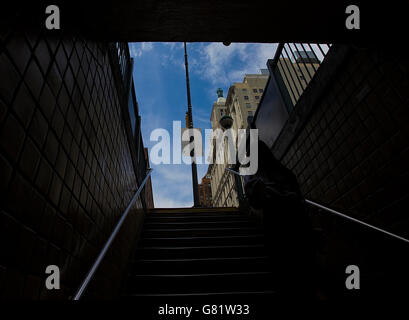 Commuter emerging from a subway in New York into the streets - Stock Image