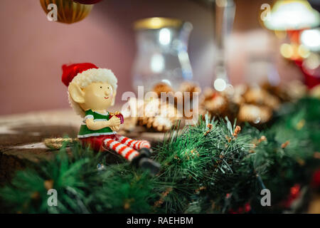 Christmas decoration - miniature toy elf with red hat sitting on a garland. - Stock Image