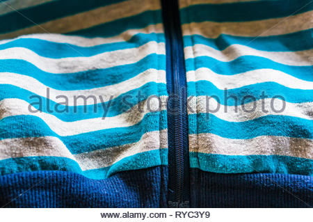 Blue and gray striped sweater close up with zipper. - Stock Image