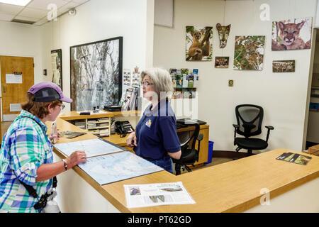 Florida Everglades Big Cypress National Preserve Oasis Visitor Center centre inside information help desk woman volunteer helping - Stock Image