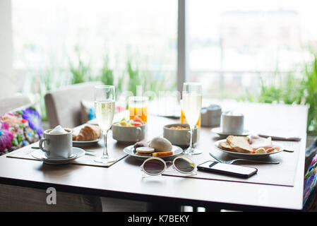 Breakfast and champagne on table in cafe - Stock Image