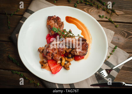 Grilled ribs with mushrooms, sweet peppers and thyme. Cafe menu on a wooden background in warm colors with copy space. - Stock Image