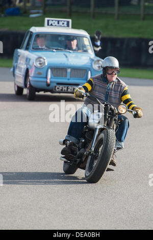 Chichester, West Sussex, UK. 14th Sep, 2013. Goodwood Revival. Goodwood Racing Circuit, West Sussex - Saturday 14th September. Biker dressed as Chino from The Wild One followed by a vintage police car takes part in the track parade of mods, rockers and police. Credit:  MeonStock/Alamy Live News - Stock Image