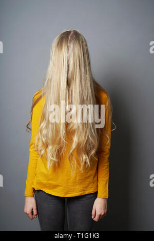 shy young woman with obscured face behind long blond hair - depressed or emabarrassed or indifferent teenage girl - Stock Image