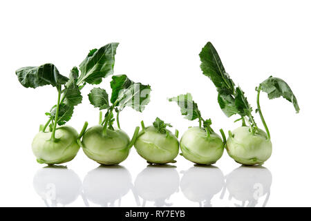Fresh kohlrabi with with leafy stems still attached on white background. - Stock Image