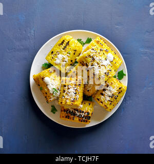 Roasted corn on the cob with sauce and parmesan over blue stone background. Top view - Stock Image