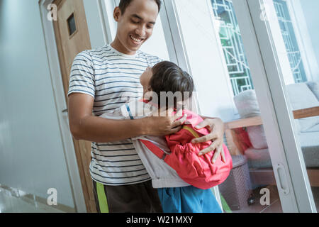 happy asian kindergarten student embrace her dad before going to school - Stock Image