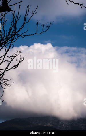 Strange white Cloud formation overhanging the edge of Athens mountains with blue sky above. Athens, Greece. - Stock Image
