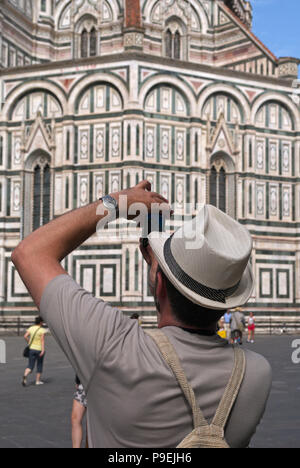 a tourist taking a photo with smartphone of the Basilica di Santa Maria del Fiore, or Duomo, in Florence, Italy - Stock Image