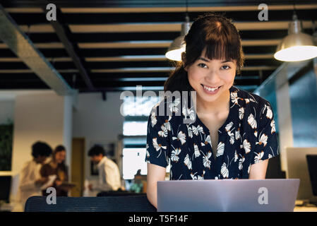 Businesswoman using laptop - Stock Image