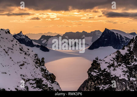 Aerial of rugged peaks and snow-covered glaciers at sunset, Juneau Ice Field, Tongass National Forest, Southeast Alaska - Stock Image