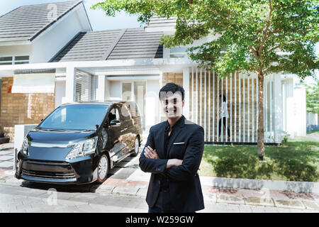 executive in his suit with luxurious car in the background. looking at camera - Stock Image