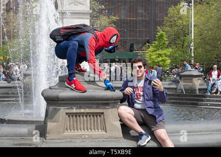 A young man in Washington Square Park taking a selfie with a performance artist dressed in a Spiderman costume. In New York City. - Stock Image