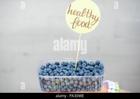 Blueberries in the transparent box with green sticker on the gray background - Stock Image