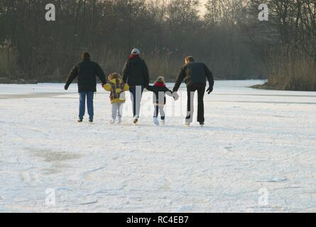 Back view family on ice-skates in Dutch landcsape - Stock Image
