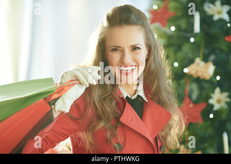 Portrait of happy trendy woman in red trench coat with shopping bags near Christmas tree - Stock Image