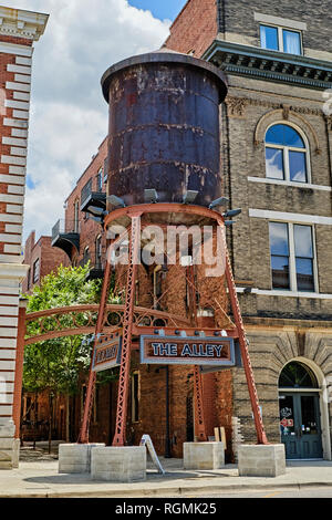 An old rooftop water tank, at street level, stands at the entrance to 'The Alley' in the entertainment district of Montgomery Alabama, USA. - Stock Image