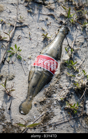 Old glass Coke bottle buried in the sand - Stock Image