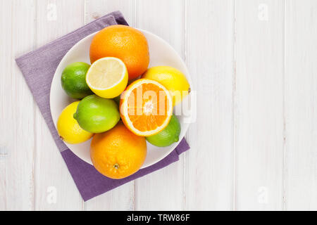 Orange, lime and lemon. Citrus fruits on white wooden table. Top view with copy space - Stock Image