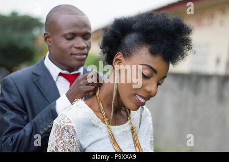 Young man in a suit carrying the chain to his wife outside. - Stock Image
