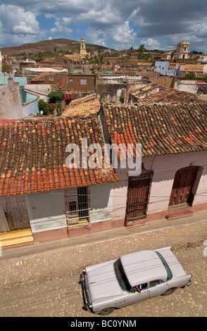 Classic American car. A cultural icon for modern day Cuba. Tiled rooftops of Trinidad, Cuba - Stock Image