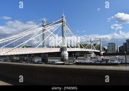 London: Albert Bridge in Chelsea on a sunny day. From the north bank of the Thames looking south to Battersea. - Stock Image