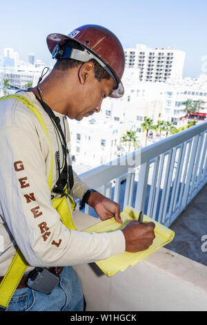Miami Beach Florida Ocean Drive Presidential Condominiums concrete renovation repair Hispanic man laborer job hard hat harness - Stock Image