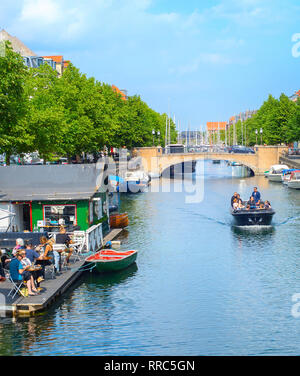 COPENHAGEN, DENMARK - JUNE 14, 2018: People in a riding boat and eating at waterfront restaurant  in Copenhagen. Copenhagen is the capital of Denmark - Stock Image