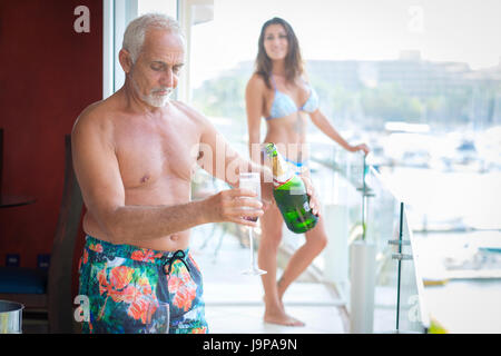 Older caucasian man pouring sparkling wine into glass for younger woman - Stock Image